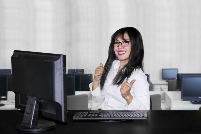 De Aziatische onderneemster geeft duimen in bureau op stock afbeeldingen