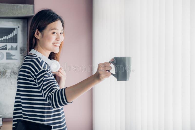 De Aziatische onderneemster neemt een koffiepauze na het werken met smili stock foto's