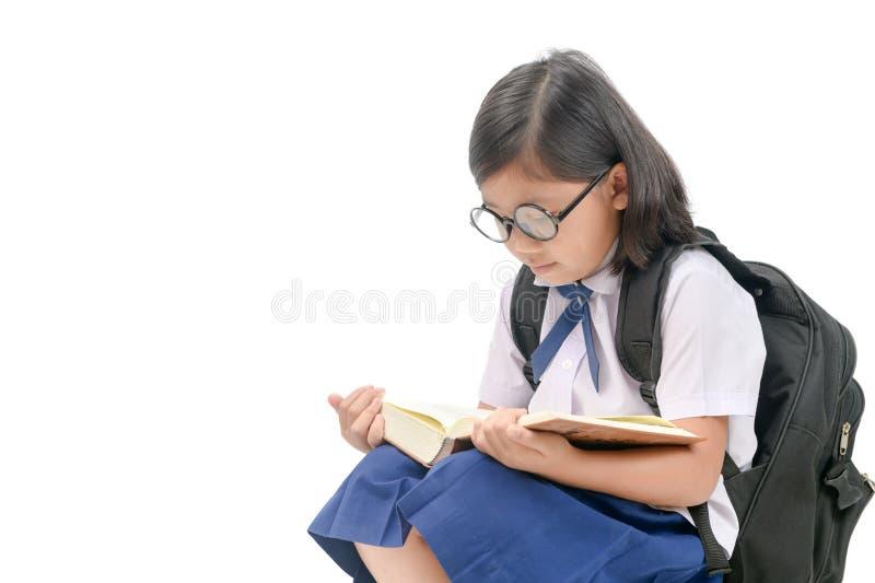 De Aziatische oogglazen die van de meisjesslijtage geïsoleerd boek lezen stock foto's