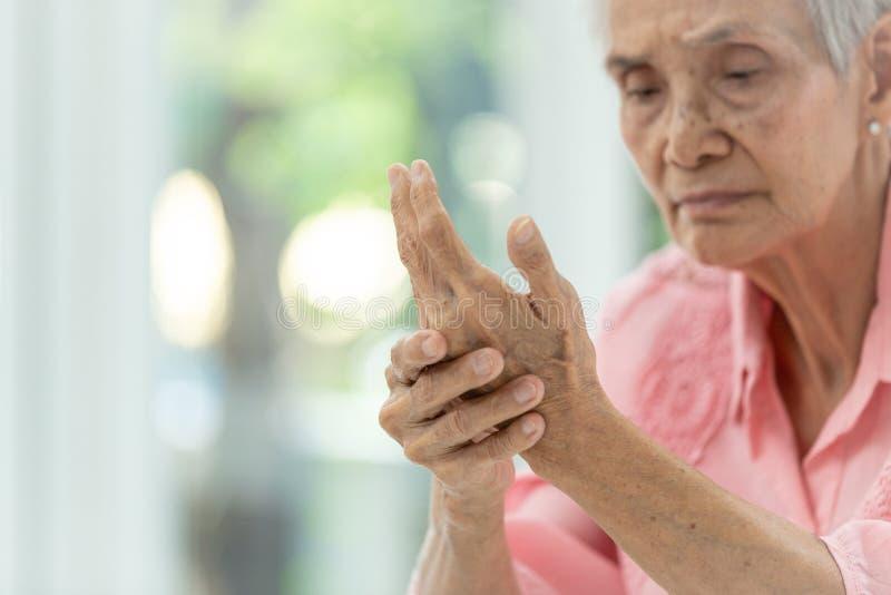 De Aziatische oude vrouw masseert haar eigen hand, Bejaarde aan pijn ter beschikking lijden, artritis, beriberi of randneuropathi royalty-vrije stock afbeelding