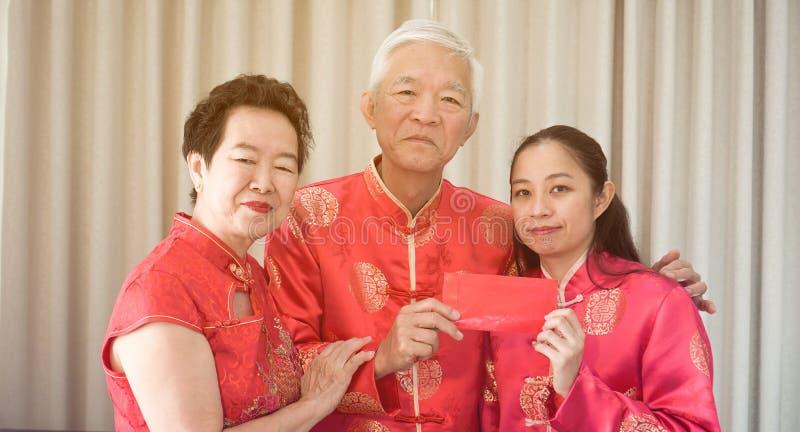 De Aziatische ouders geven rood wikkelen aan dochter Chinees Nieuwjaar stock fotografie