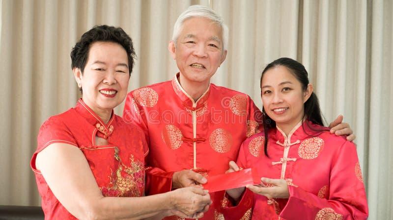 De Aziatische ouders geven rood wikkelen aan dochter Chinees Nieuwjaar royalty-vrije stock foto
