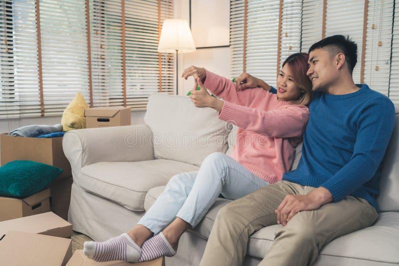 De Aziatische paar bewegende kleren en vele voorwerpen van oud huis aan hun nieuw huis en ontspannen op bank in woonkamer bij hun stock foto's