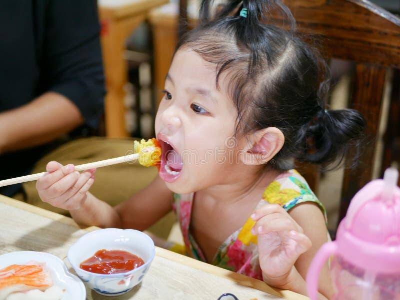De Aziatische proevende tomatensaus van het babymeisje voor het eerst in haar leven stock afbeelding