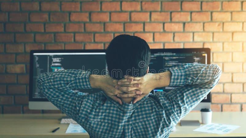 De Aziatische programmeursmens ontspant en bekijkt de code inzake het computerscherm in het bureau stock afbeeldingen