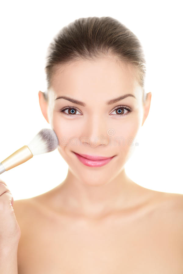 De Aziatische schoonheidsvrouw die make-up zetten bloost op gezicht royalty-vrije stock foto's