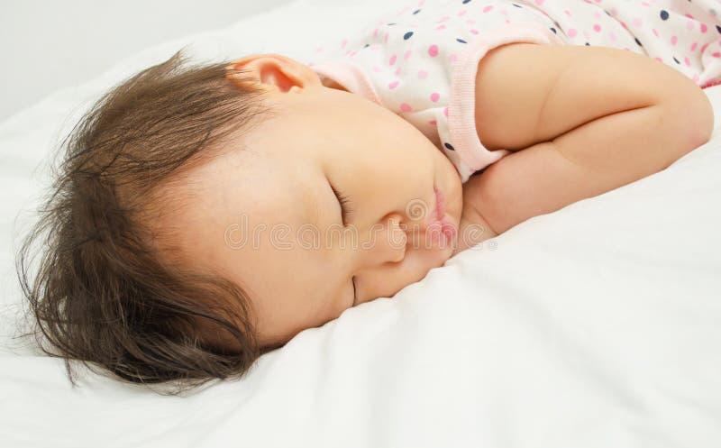 De Aziatische slaap van het babymeisje op bed royalty-vrije stock afbeelding