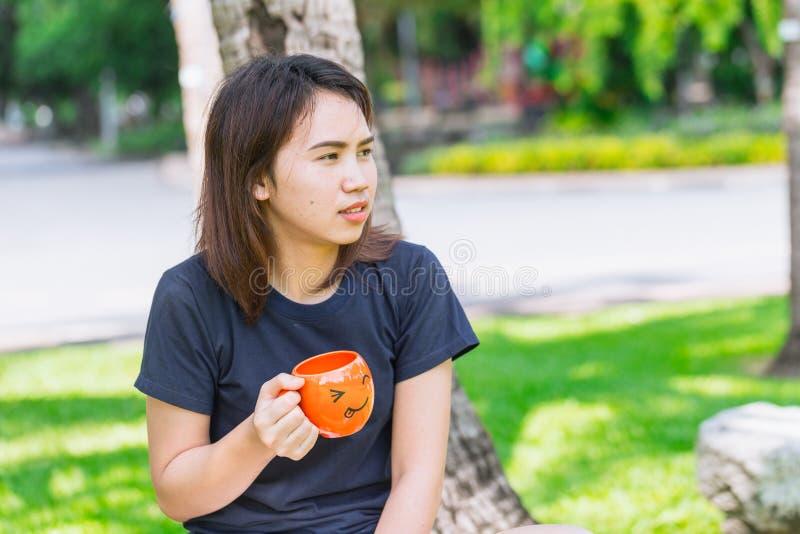 De Aziatische smileymok van de tienerholding geniet van drinkend ochtendkoffie openlucht stock afbeeldingen