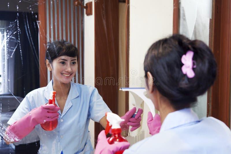 De Aziatische spiegel van meisjeschoonmaken in badkamers royalty-vrije stock foto's