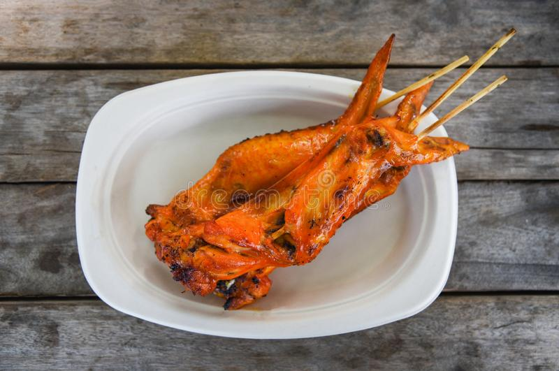 De Aziatische stijl roosterde kippenvleugel op dienblad houten achtergrond/de Thaise roosterende stokken van de kippenvleespen royalty-vrije stock foto