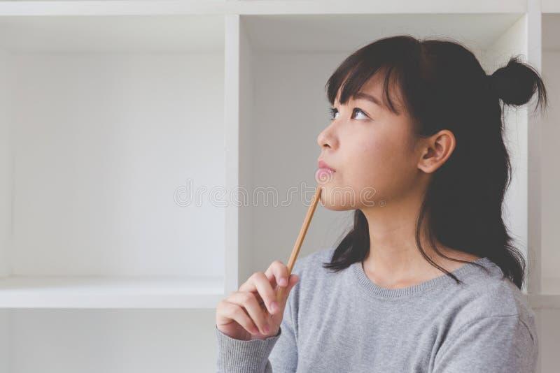de Aziatische student die van de meisjes vrouwelijke tiener iets naast boe-geroep denken stock fotografie