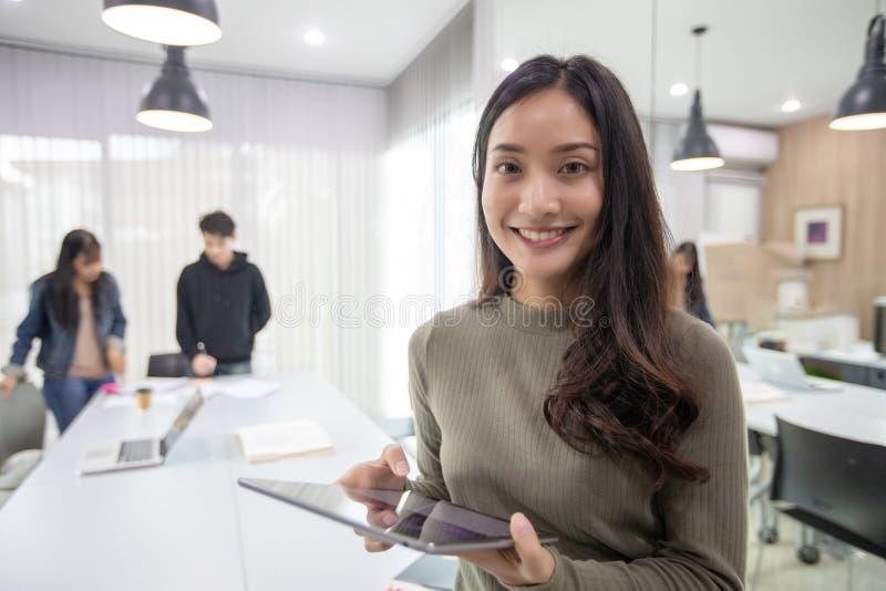 De Aziatische Studentesglimlach en heeft pret en het gebruiken van smartphone en tablet het ook helpt om ideeën in het werk en he stock afbeeldingen