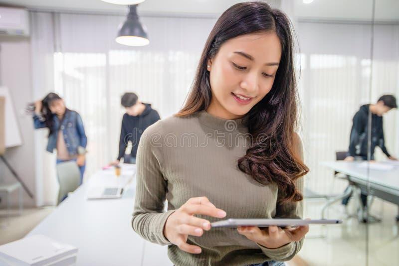 De Aziatische Studentesglimlach en heeft pret en het gebruiken van smartphone en tablet het ook helpt om idee?n in het werk en he royalty-vrije stock foto