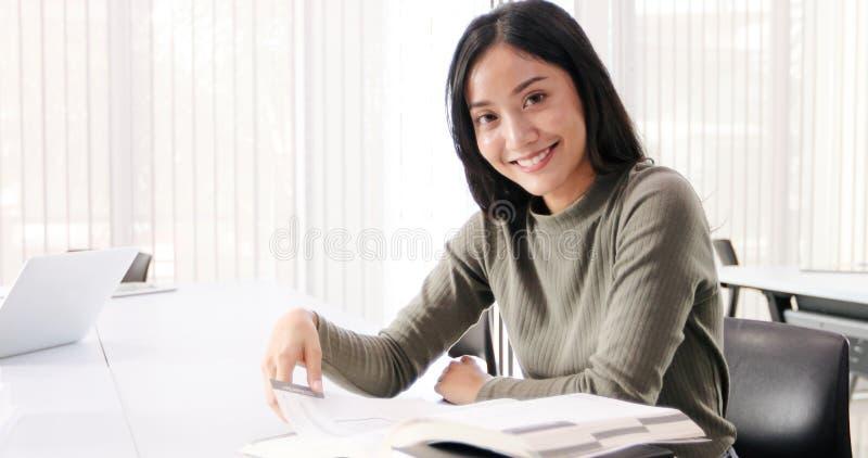 De Aziatische de Studentesglimlach en lezing boeken en gebruikend notitieboekje voor hulp om idee?n in het werk en het project te stock afbeelding