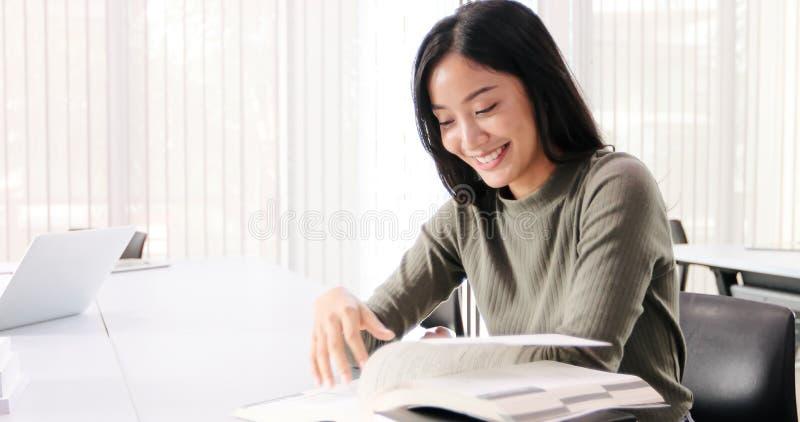 De Aziatische de Studentesglimlach en lezing boeken en gebruikend notitieboekje voor hulp om idee?n in het werk en het project te stock foto's