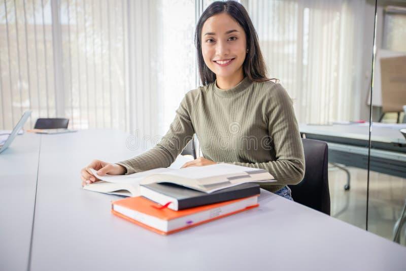 De Aziatische de Studentesglimlach en lezing boeken en gebruikend notitieboekje voor hulp om idee?n in het werk en het project te stock foto