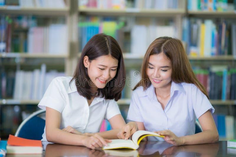 De Aziatische studie van de damestudent en doet het huiswerk in bibliotheek in Universi stock foto's