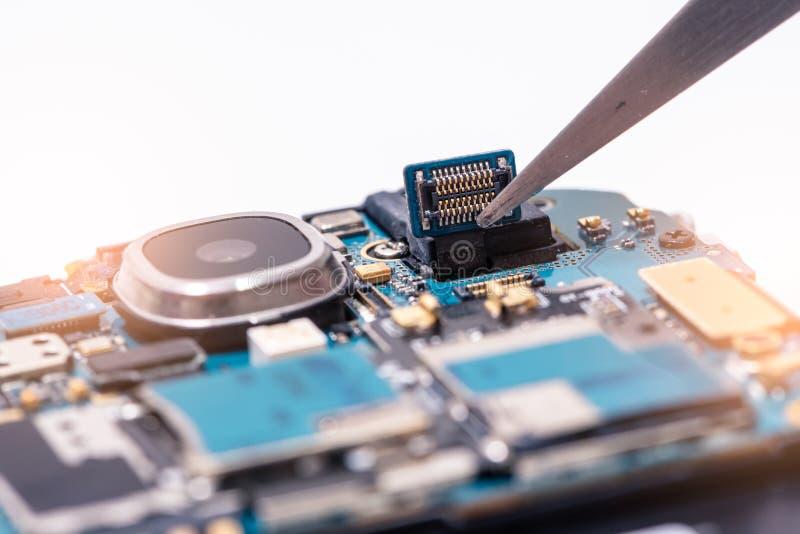 De Aziatische technicus die smartphone` s motherboard in het laboratorium met exemplaarruimte herstellen stock afbeelding