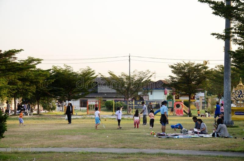 De Aziatische Thaise familie ontspant spel met picknick en mensen die oefening aanstoten bij speelplaats op yard in openbaar tuin stock fotografie