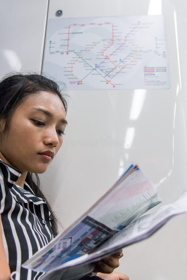 De Aziatische toerist bekijkt de kaarten in de metro stock foto