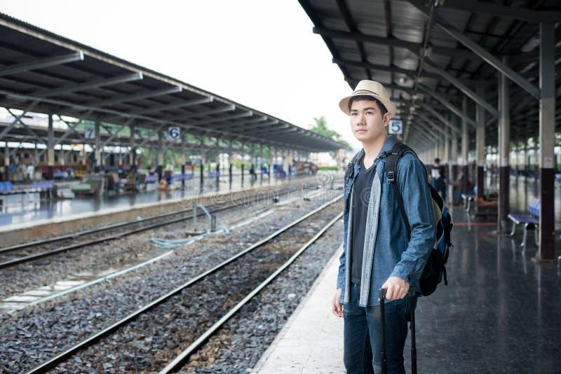 De Aziatische trein van het jonge mensenwachten bij post stock fotografie