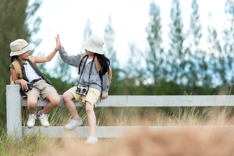 De Aziatische twee kinderen heffen geven me vijf en zitting in openlucht op de witte omheining, avontuur en toerisme voor bestemm stock afbeelding