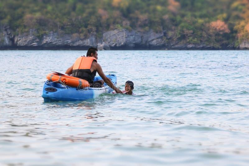 De Aziatische vader en de dochter onderwijzen en leiden het levenswacht of redding op het strand op stock afbeelding
