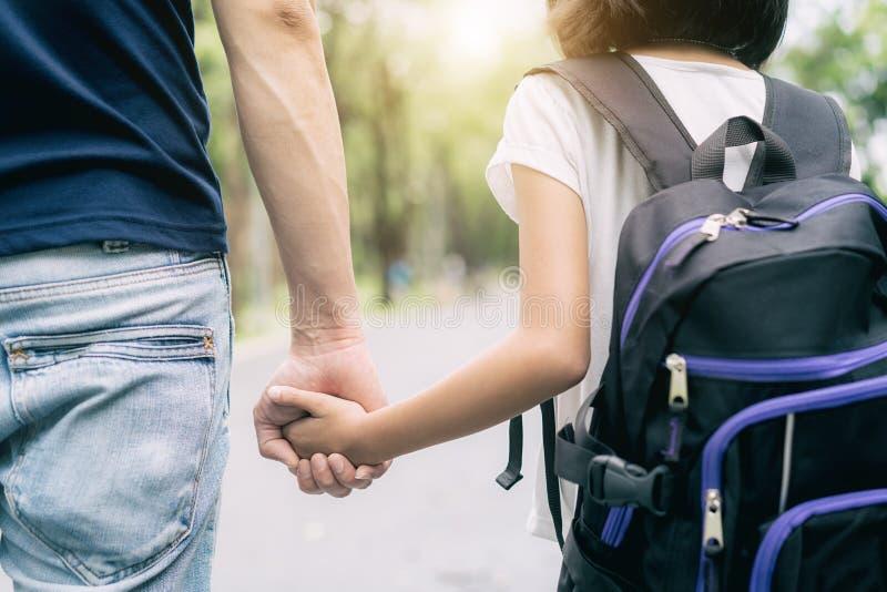 De Aziatische vader` s hand leidt zijn meisjeskind in de zomerpark gaat naar sch royalty-vrije stock fotografie