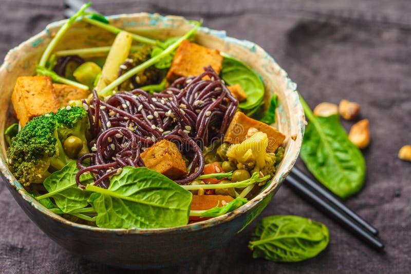De Aziatische veganist beweegt gebraden gerecht met tofu, rijstnoedels en groenten, donkere achtergrond royalty-vrije stock foto's