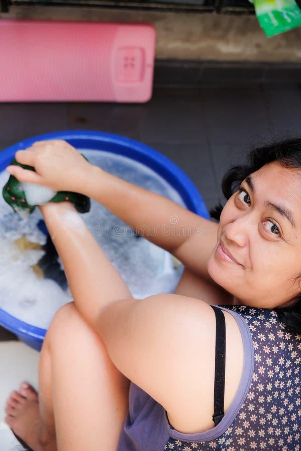 De Aziatische Volwassen Vrouw geniet van thuis doend Wasserij De was van de hand stock fotografie