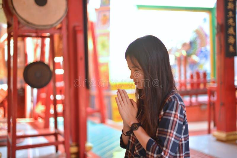 De Aziatische vrouw bidt eerbied aan Chinese Boedha in Chinese tempel stock afbeelding