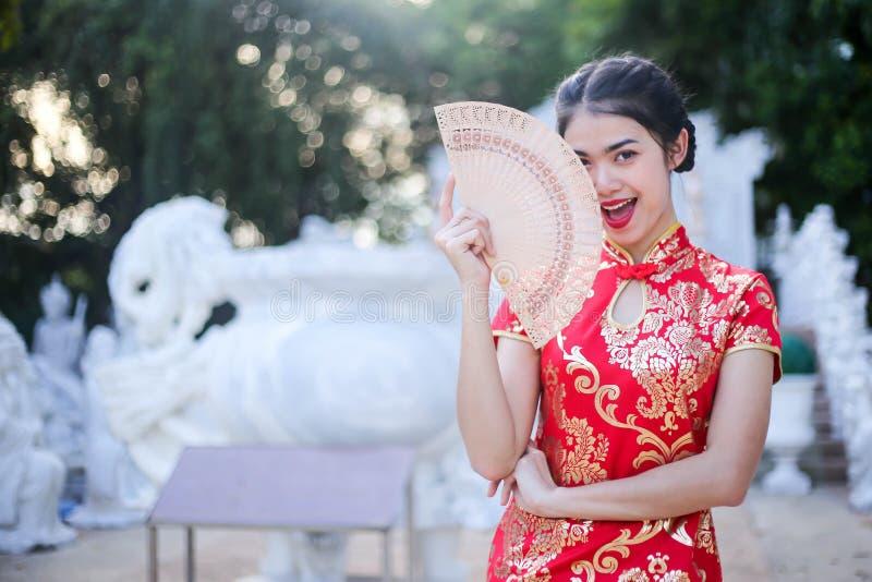 De Aziatische vrouw in Chinees kleedt traditioneel met gebaar van gelukwens die rood hart houden stock foto