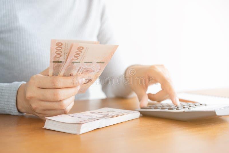 De Aziatische vrouw die van de close-uphand van de calculator het tellen en telling geld in huis gebruiken stock foto's