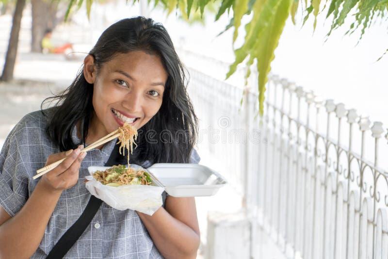 De Aziatische vrouw eet typisch Birmaans voedsel op een straat stock afbeeldingen