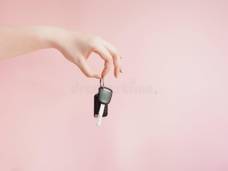 De Aziatische vrouw geeft haar autosleutel aan nieuwe autoeigenaar door wi van de schoonheidshand stock fotografie