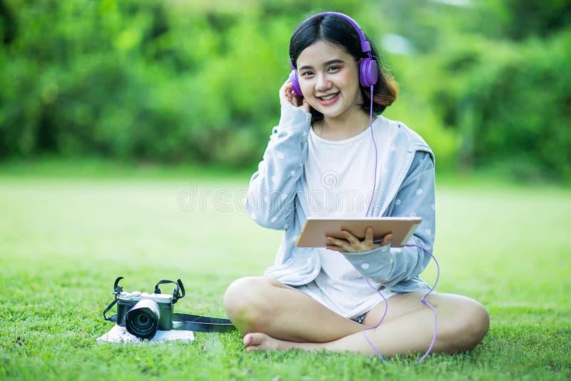 De Aziatische vrouw geniet van luister aan muziek in de tuin royalty-vrije stock afbeeldingen