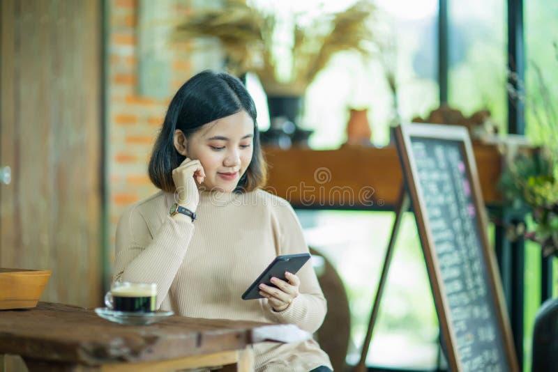 De Aziatische vrouw geniet van met cellphone in de koffie royalty-vrije stock afbeeldingen