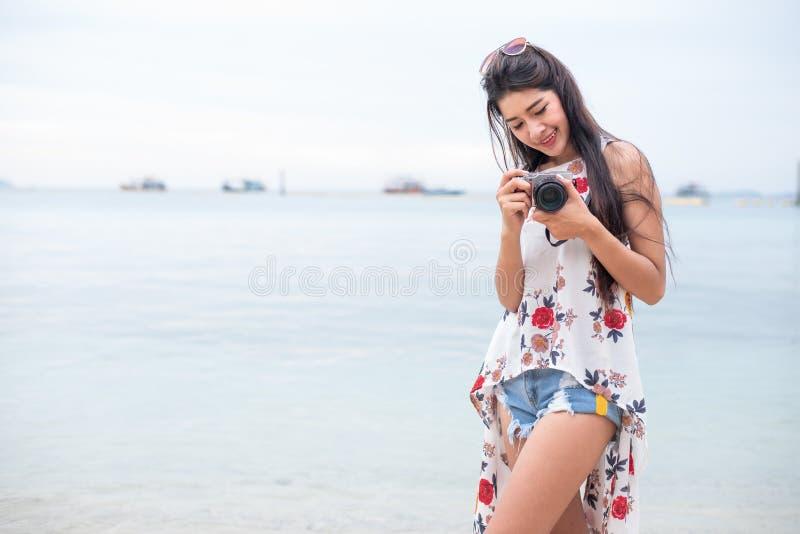 De Aziatische vrouw geniet van neemt foto door digitale camera bij strand single royalty-vrije stock afbeelding