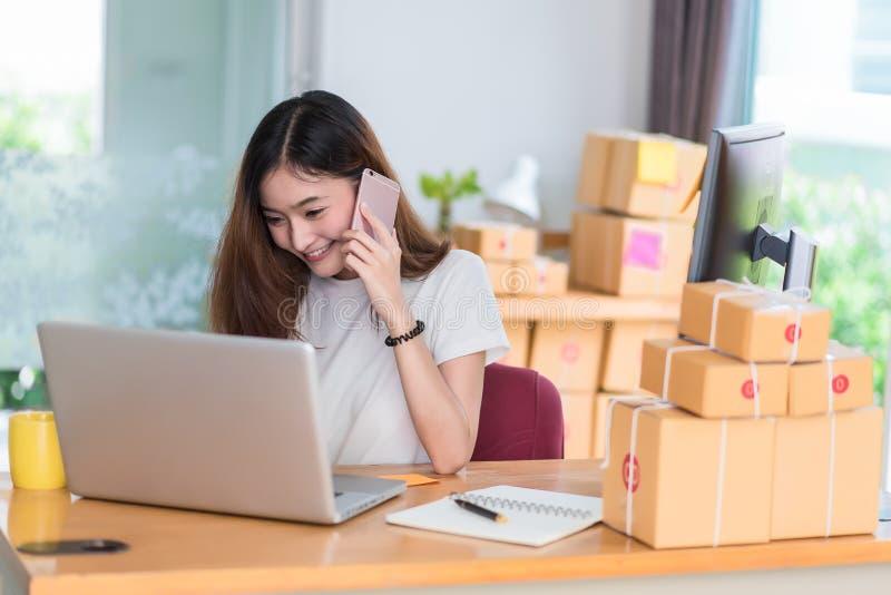De Aziatische vrouw geniet zich van terwijl het gebruiken van Internet op laptop en telefoon in bureau Zaken en marketing en part royalty-vrije stock afbeeldingen