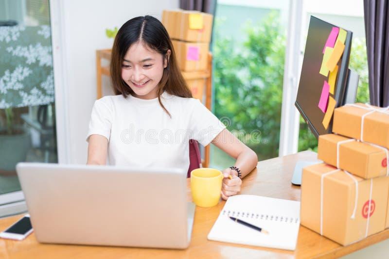 De Aziatische vrouw geniet zich van terwijl het gebruiken van Internet op laptop en telefoon in bureau Zaken en marketing en part stock afbeeldingen