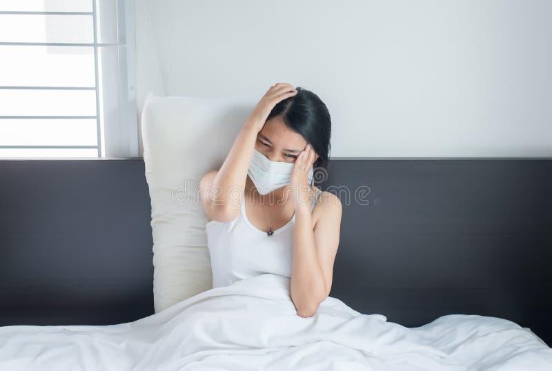 De Aziatische vrouw heeft een hoofdpijn die beschermend masker met koude het blazen en lopende neus, Ziek wijfje gebruiken omhoog royalty-vrije stock afbeeldingen