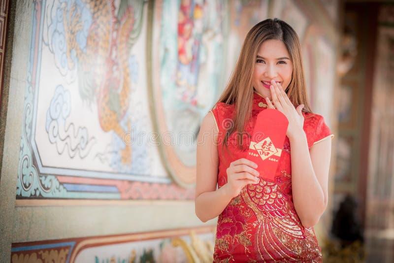 De Aziatische vrouw in het Chinese 'Gelukkige' couplet van de kledingsholding (Ruggegraat stock foto