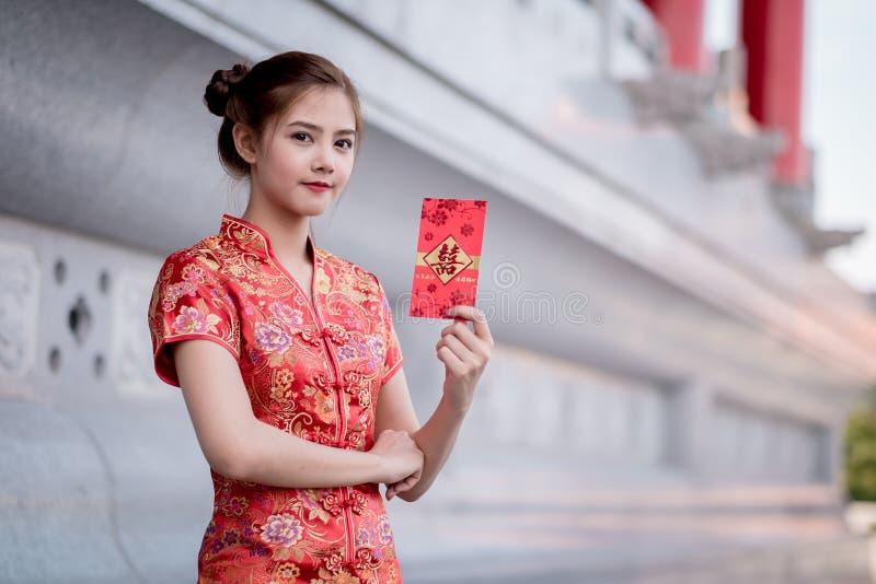 De Aziatische vrouw in het Chinese 'Gelukkige' couplet van de kledingsholding (Ruggegraat stock afbeelding