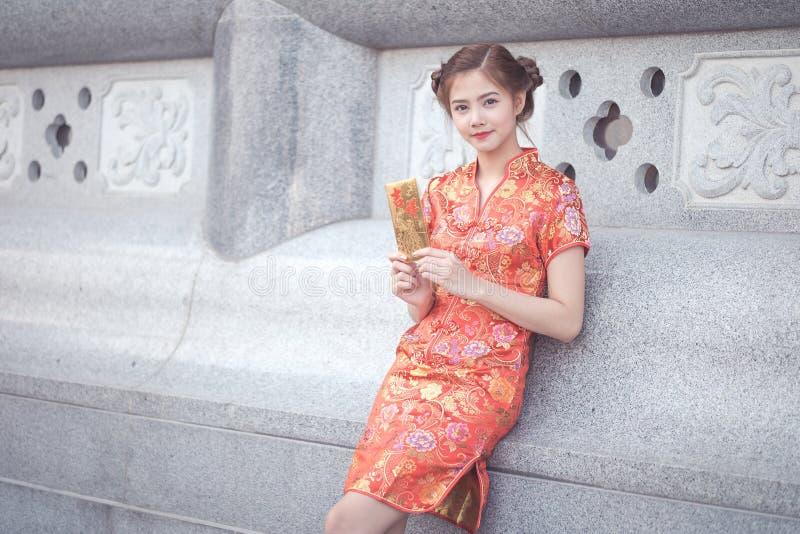 De Aziatische vrouw in het Chinese 'Gelukkige' couplet van de kledingsholding (Ruggegraat stock fotografie