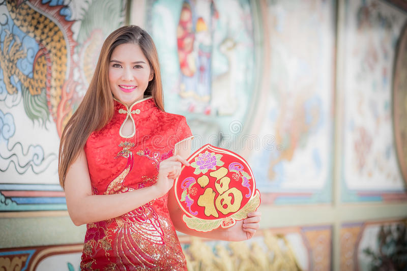 De Aziatische vrouw in het Chinese 'Gelukkige' couplet van de kledingsholding (Ruggegraat stock afbeeldingen