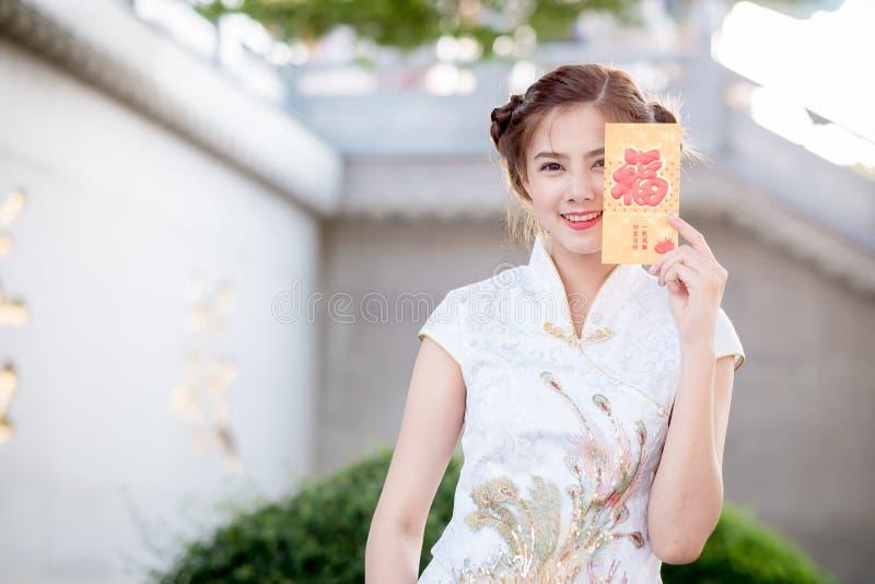De Aziatische vrouw in het Chinese 'Gelukkige' couplet van de kledingsholding (Ruggegraat royalty-vrije stock foto