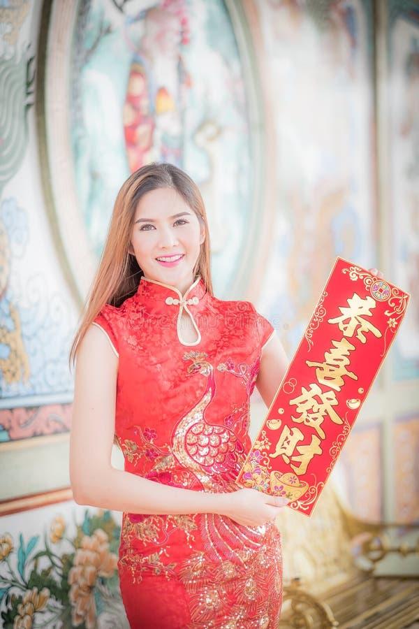 De Aziatische vrouw in het Chinese 'sterke' couplet van de kledingsholding (Kin stock foto's