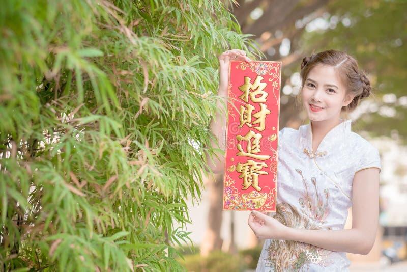 De Aziatische vrouw in het Chinese 'sterke' couplet van de kledingsholding (Kin royalty-vrije stock fotografie