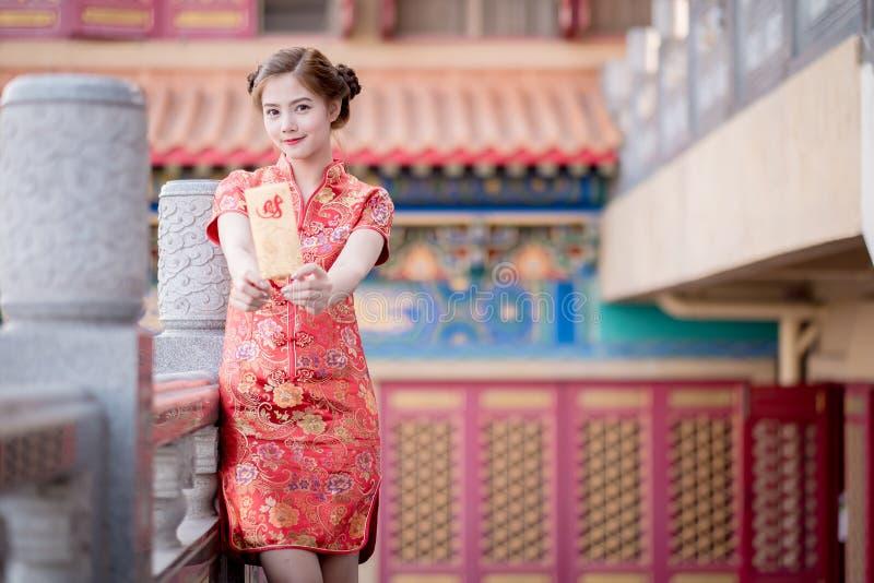 De Aziatische vrouw in het Chinese 'Winstgevende' couplet van de kledingsholding (C stock afbeeldingen