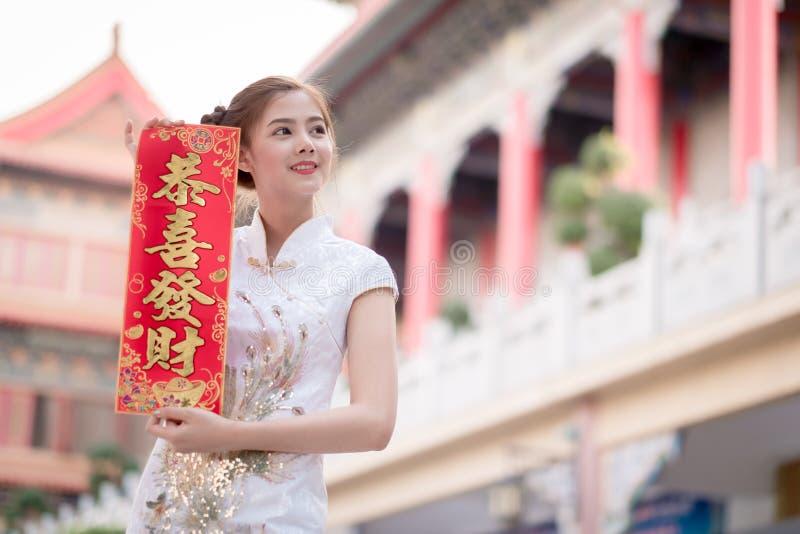 De Aziatische vrouw in het Chinese 'Winstgevende' couplet van de kledingsholding (C royalty-vrije stock foto